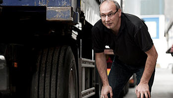 truck driver inspecting wheels of trailer